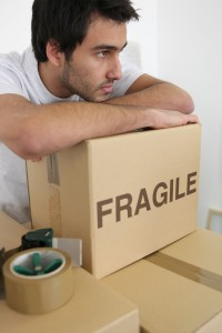 man leaning on stack of boxes